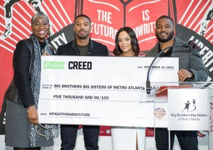 Big Brothers Big Sisters President/CEO Janice McKenzie-Crayton receives a check from 'Creed' stars Michael B. Jordan, Tessa Thompson, and writer/director Ryan Coogler during Big Brothers Big Sisters of Metro Atlanta mural unveiling on November 10, 2015 in Atlanta, Georgia.